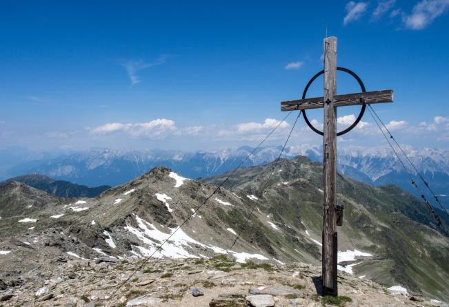 Gipfelkreuz am Rosenjoch mit Blick nach Norden in Richtung Kreuzspitze und Glungezer