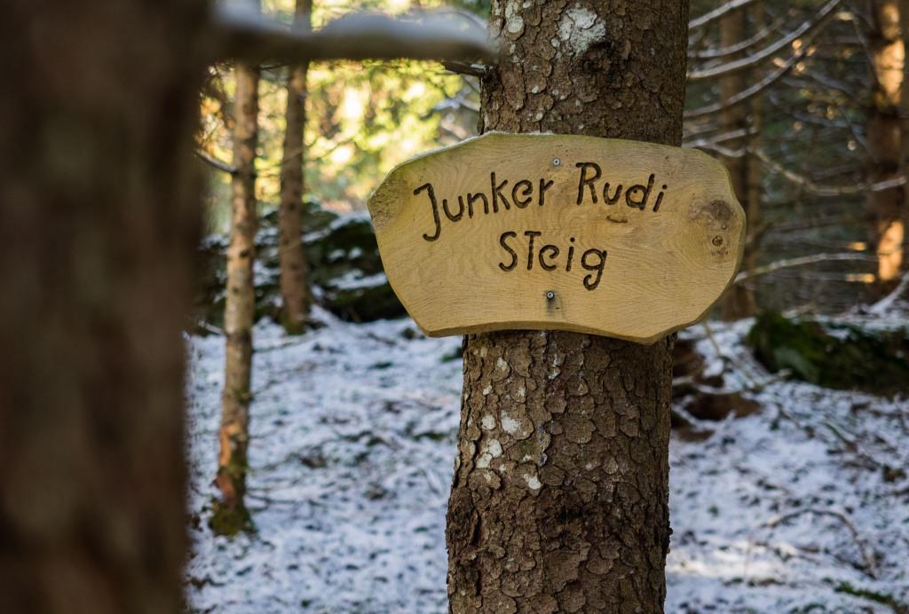 """Schild """"Junker Rudi Steig"""" auf einem Baum"""