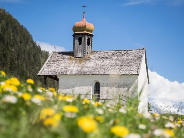 Kapelle der Stiftsalm in blühender Blumenwiese